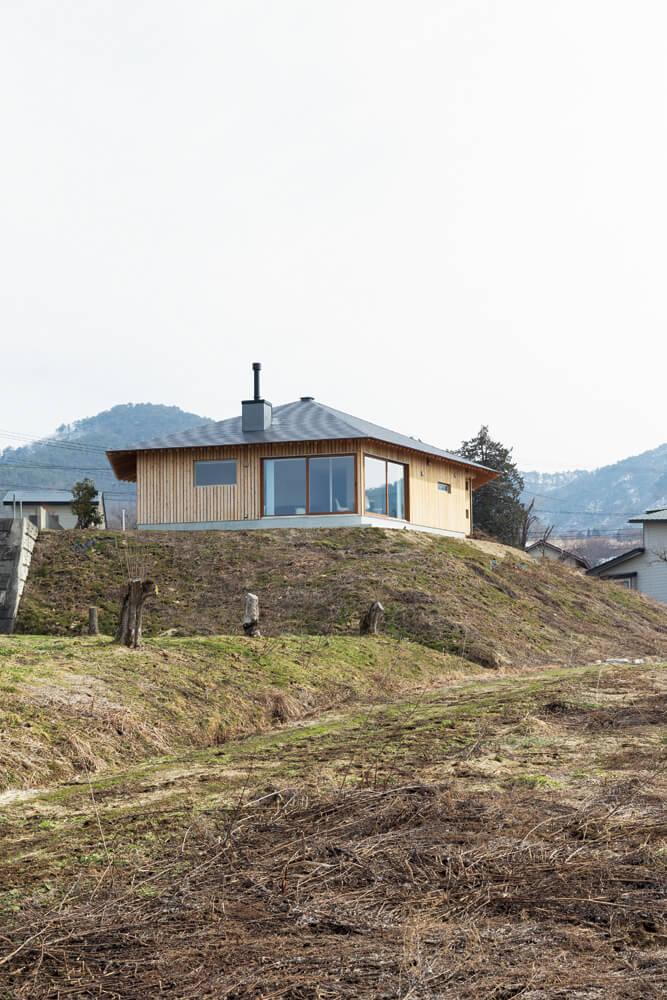 3棟分が建つほどの広さと盛土によって高低差のある敷地を生かし、山を望める方向に大きく開く配置計画とした