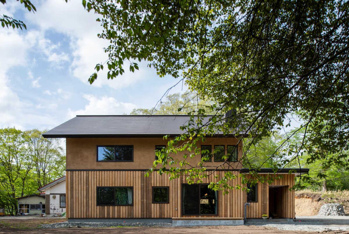 雑木林に包まれるようにして建つNさん一家の住まい。外壁は、1階に施主支給のカラマツ板を張り、2階はカラマツ材と色合いを合わせたモルタルで仕上げられている