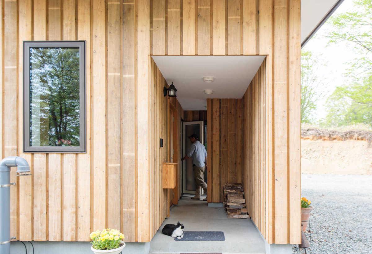 建物の中に組み込むようにしつらえた玄関ポーチは、勝手口にもつながる。雨や雪が当たりにくいポーチは、薪置き場にも活用されている