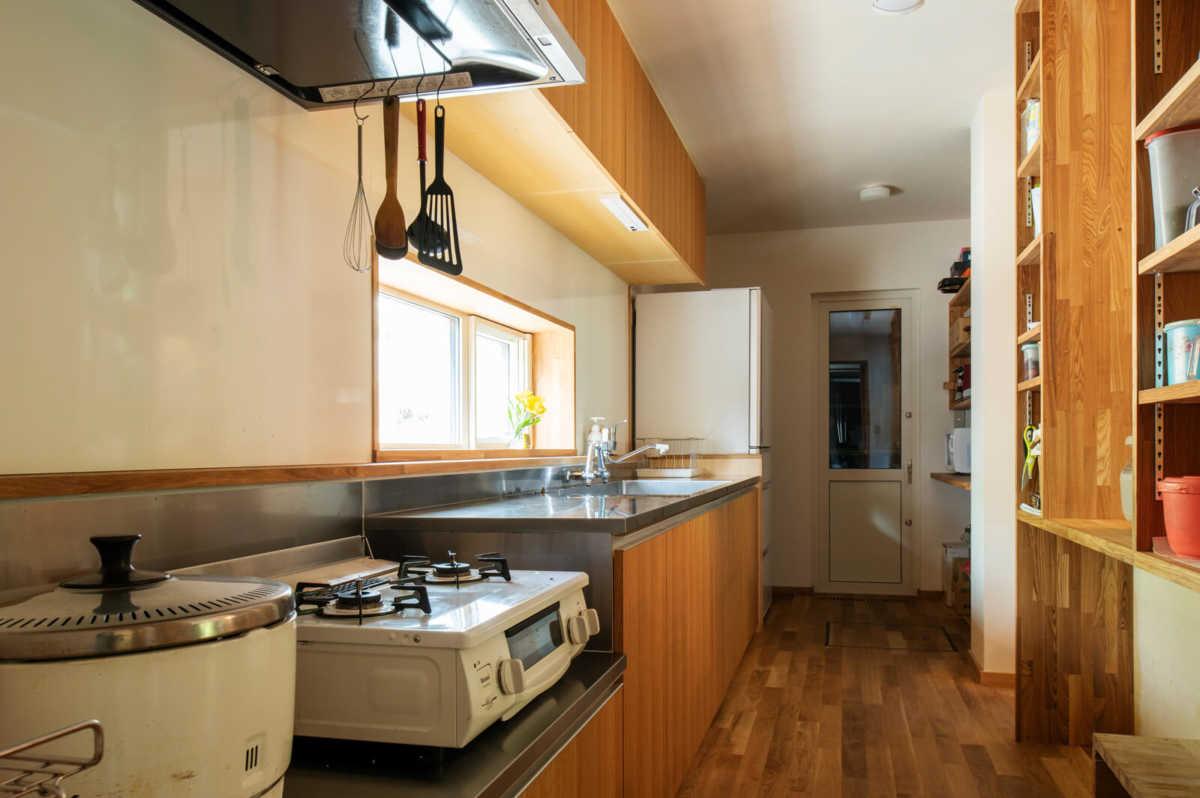 料理が好きなお母さんのために、キッチンは造作で旧宅と同じような環境、設備を整えた。大鍋で煮炊きがしやすいよう、ガスコンロを置く台は低めに設えた。背面の造作収納は使い勝手をより良くするため、施工中に大工さんと何度も調整をした。突き当たりは、畑の野菜や保存食をたっぷりしまえる土間仕様の食品庫