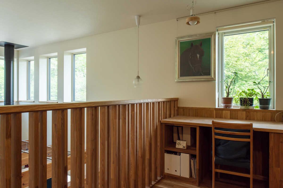 吹き抜けに面した2階階段ホールには、奥さんお気に入りの雑木林と小川を望む読書コーナーが設けられている。造作机は可動式