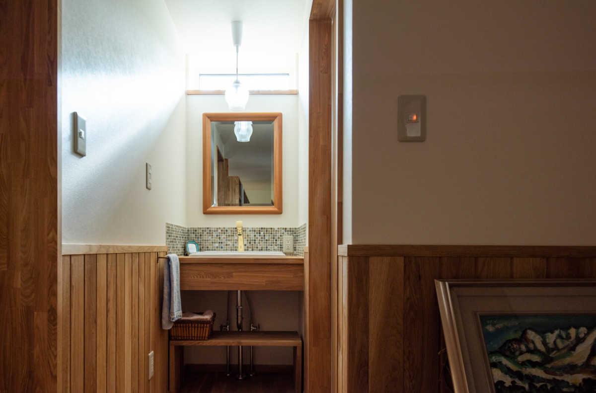 採光窓からこぼれる西陽が美しい2階洗面所。洗面台は造作。3世代同居のNさん宅は、1階に設けた水まわりとトイレ、キッチンは共用だが、家族が多いため、2階にも洗面とトイレを別途設けている