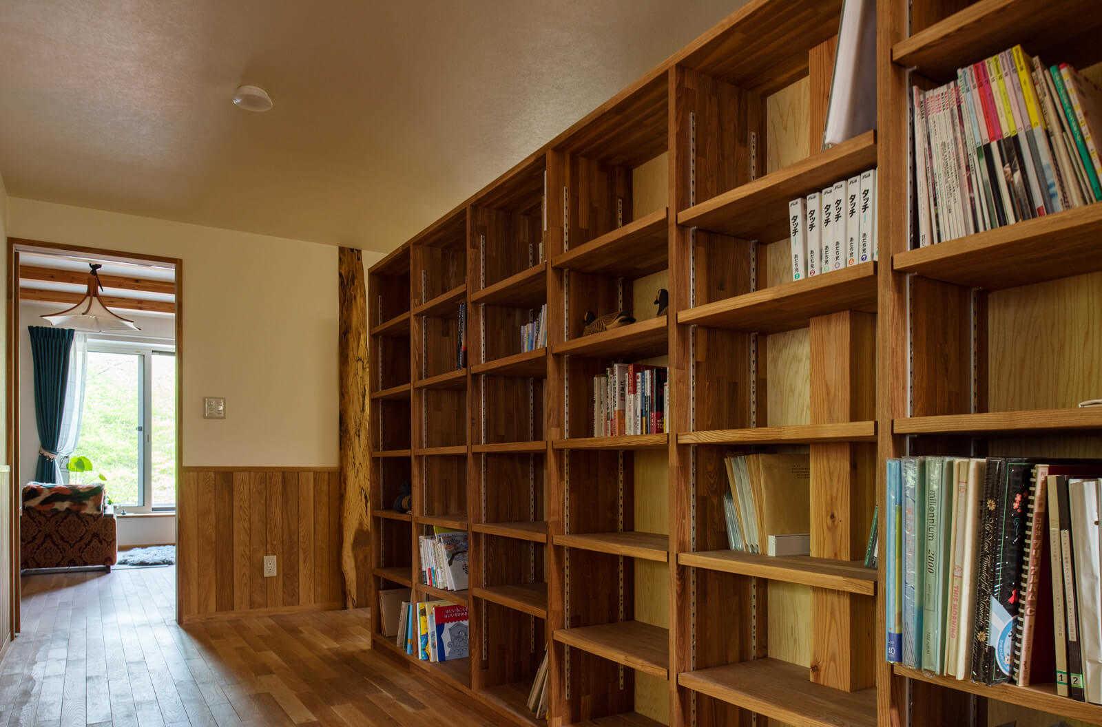 2階階段ホールに設けた家族共用の造作本棚には、アルバムや蔵書を収め、図書館のような雰囲気