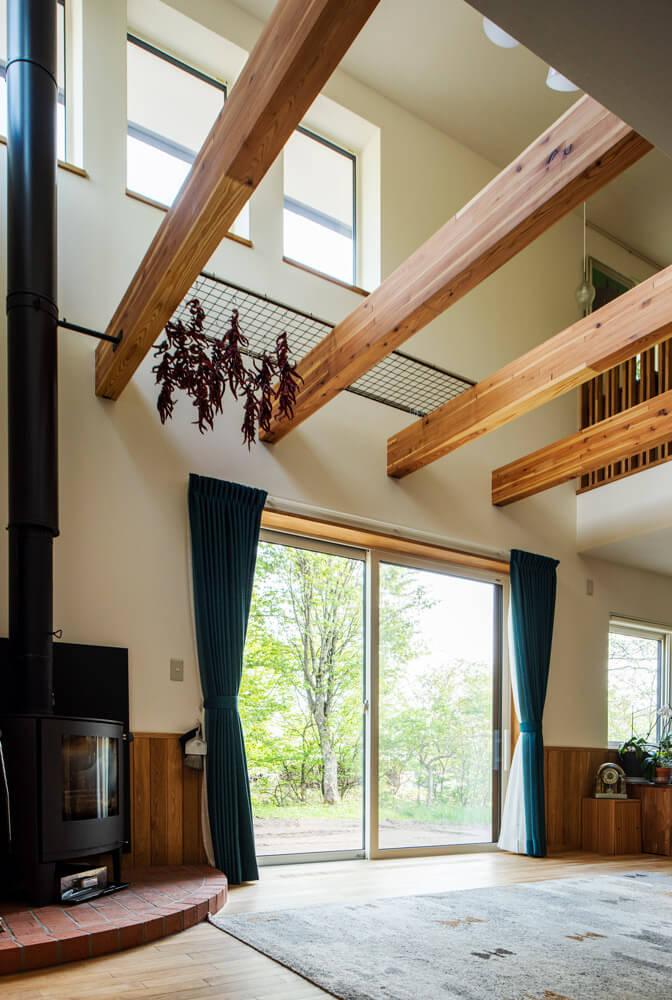 高い吹き抜けと化粧梁、薪ストーブが開放的な雰囲気をつくりだすリビング。冬には炎のまわりに家族が自然と集まる