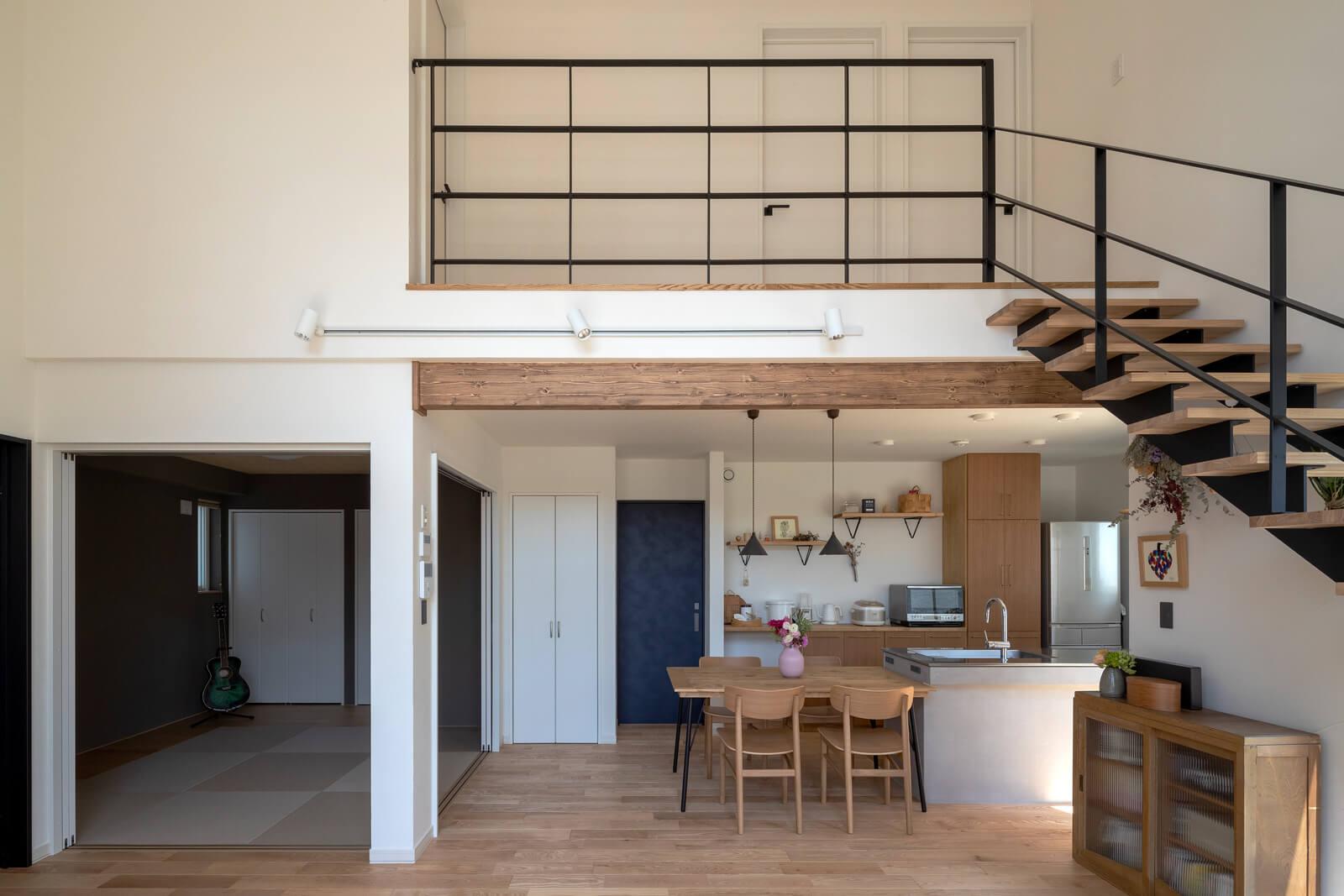ご夫妻の希望どおり、ヨーロピアンアッシュの無垢フローリングと天然石塗り壁を採用したLDKは、アイアンの黒をアクセントに。リビングの一角に設けた和室も琉球畳と板畳を採用し、モダンに仕上げた
