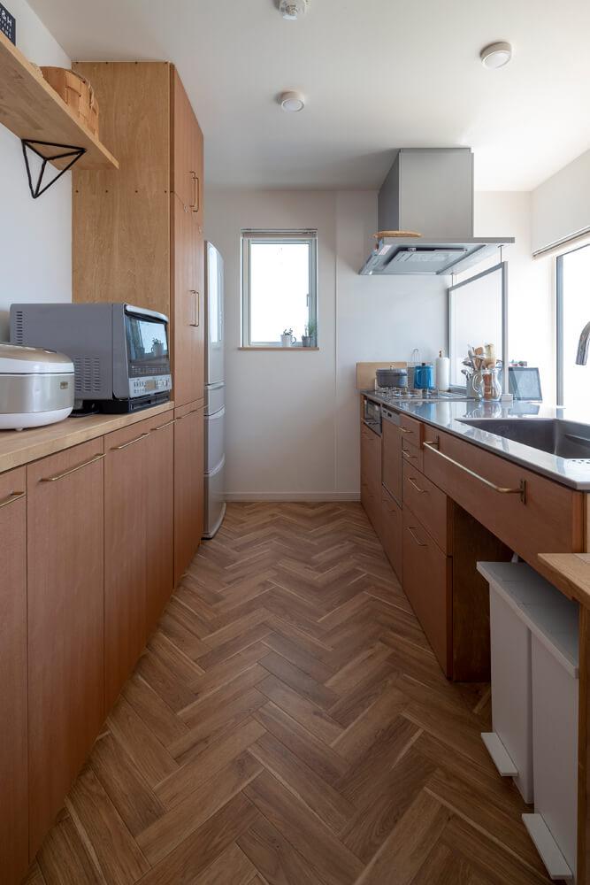 容量たっぷりの背面収納を備えた造作キッチン。カバの集成材や突き板を用い、すっきりシンプルに仕上げた。床はメンテナンスがしやすいクッションフロアを採用。リビング・ダイニング側は、奥さんの要望でモルテックス仕上げとした
