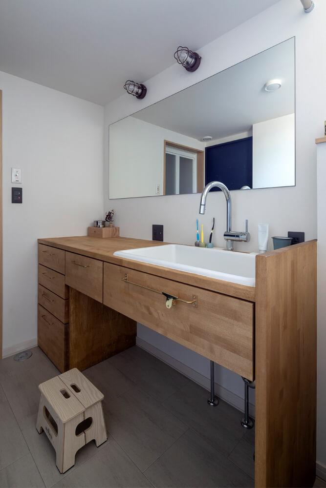実験用シンクを採用した洗面台も造作。左手奥には、忙しい奥さんのために、洗濯物をたっぷり干せる洗濯室も設けた。「家事効率のいい住まいを希望していましたが、提案された洗濯室はとても便利で重宝しています」と奥さん