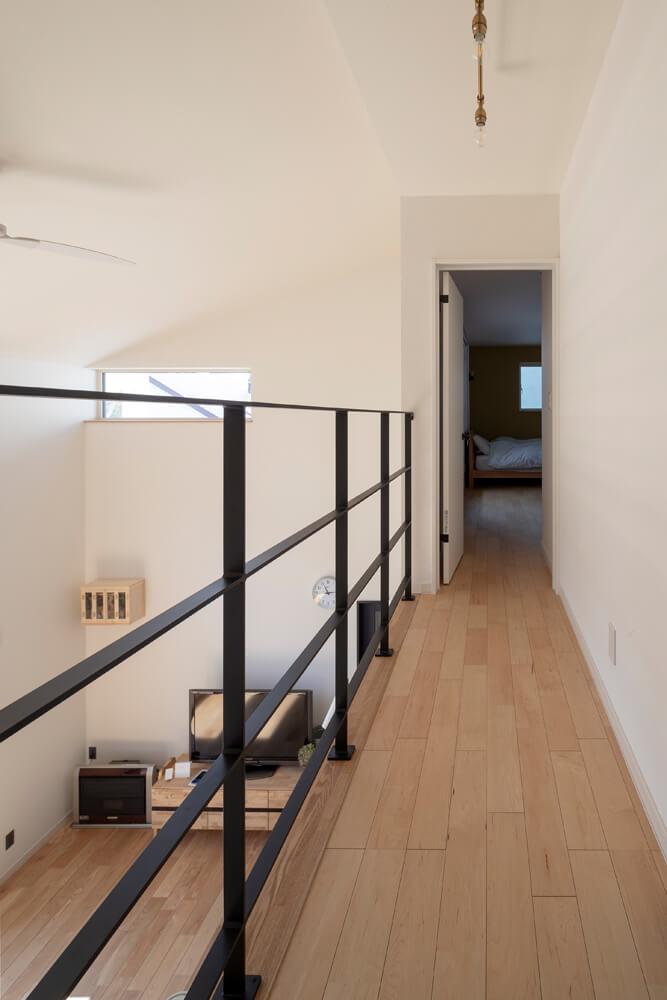 リビングの吹き抜けに沿ってブリッジ状に伸びる階段ホール。突き当たりは、ウォークインクローゼットを備えた主寝室
