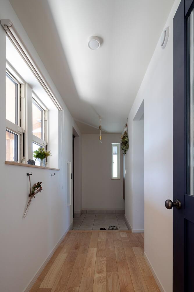 ポーチ側に設けた窓から外光が入り込む明るい玄関ホール。玄関まわりをいつでもすっきりと保てるよう、容量たっぷりのシューズクロークを土間続きに設けた