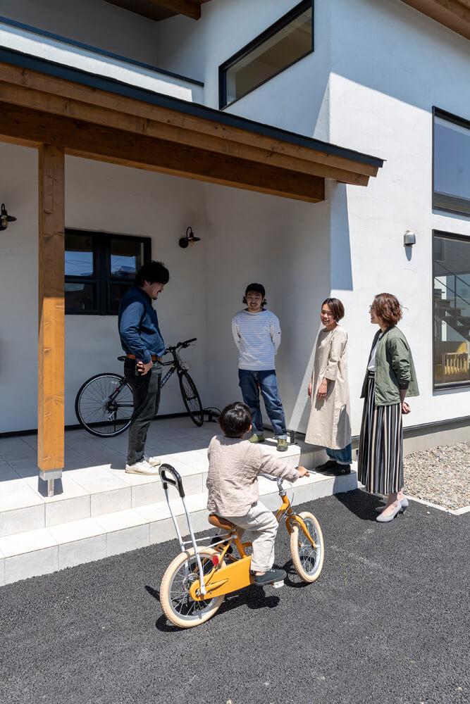 玄関ポーチで家づくりの思い出を語り合うプラスワイドの清水さん(左端)とIさんご夫妻、インテリア担当スタッフの牧野伸子さん