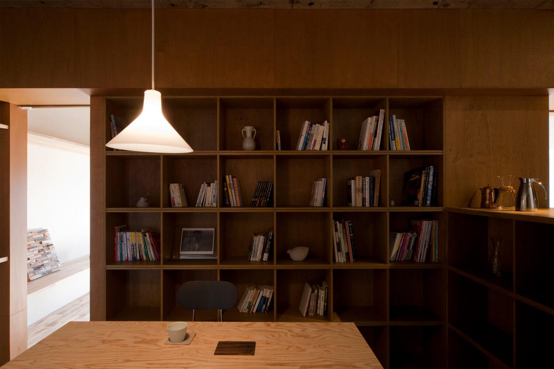 古いマンションのリノベーション。既存の間仕切り壁を取り除き、本棚で空間を区切っている。落ち着いたダイニングスペース