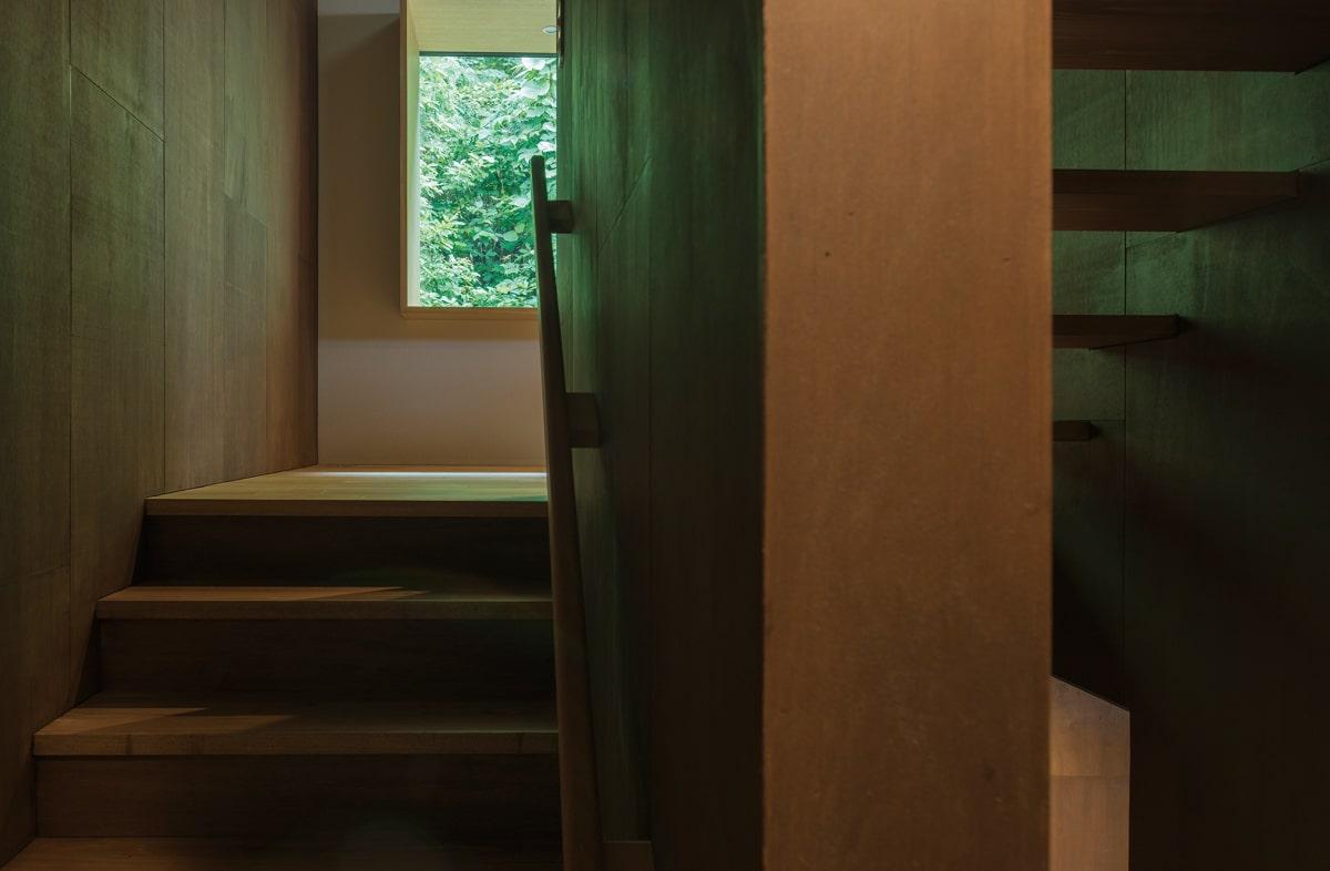 敷地の傾斜を生かしたスキップフロアの住宅。玄関から階段を上がっていくと、窓越しに鮮やかな緑が迎える
