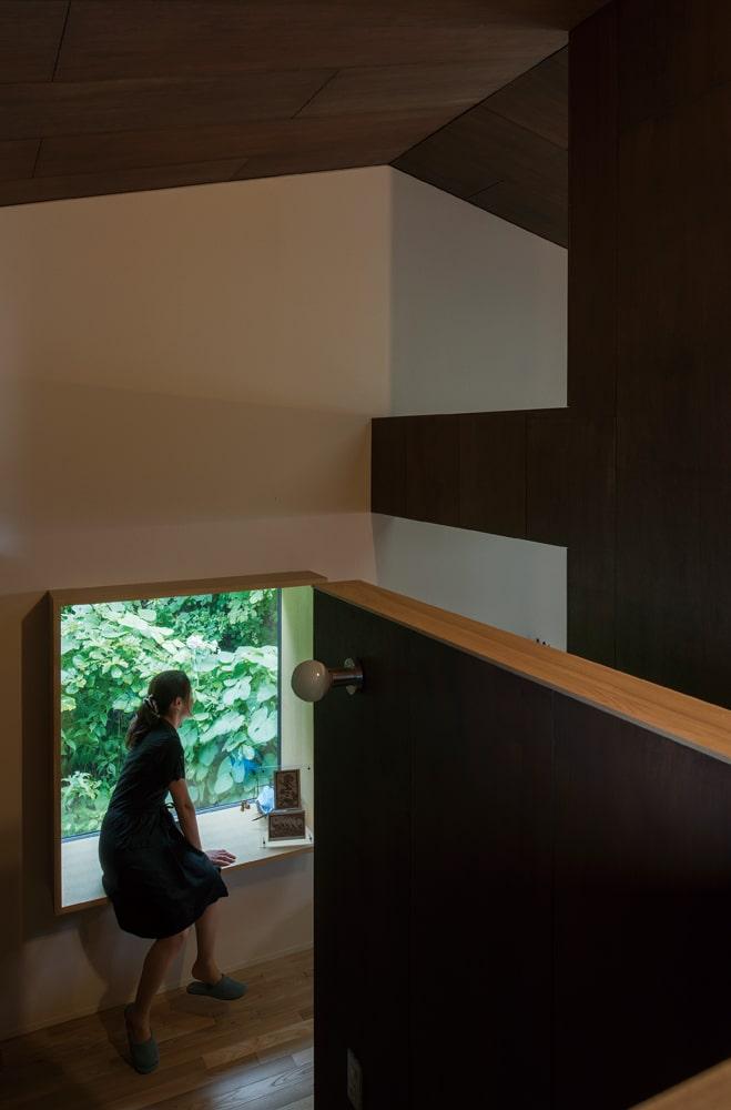2階の階段踊り場を見下ろす。奥行きを設けた窓辺に腰掛け、読書をしたりお茶を飲んだり