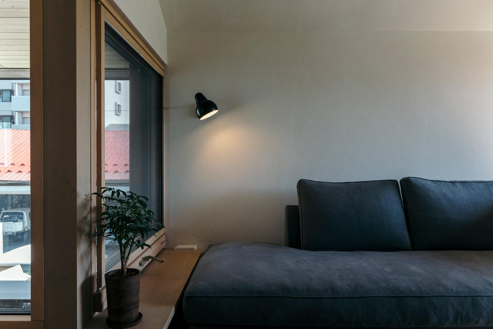 白壁と木窓とリネンのソファの組み合わせが美しい。読書を楽しめるようスポットライトを設けた