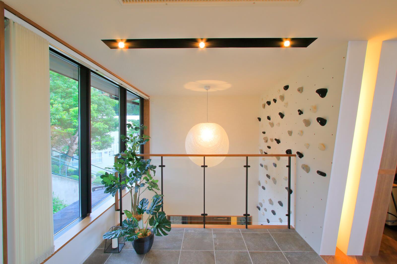 玄関からボルダリングの壁が続く吹き抜けのインナーガーデン。ピアノを設置したステージに面している