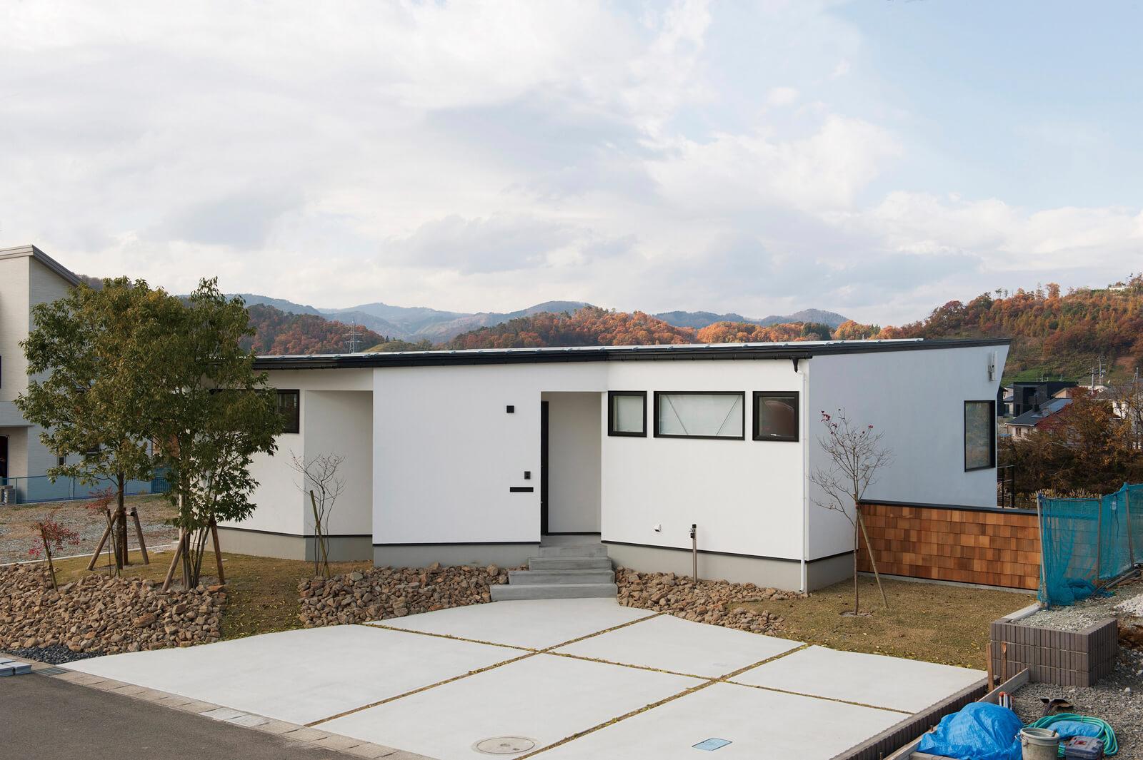 南東側から見た外観。フラットに近い屋根と白い外壁が印象的。道路に面しているので、あえて窓は小さくし、玄関の目隠しに壁を設置