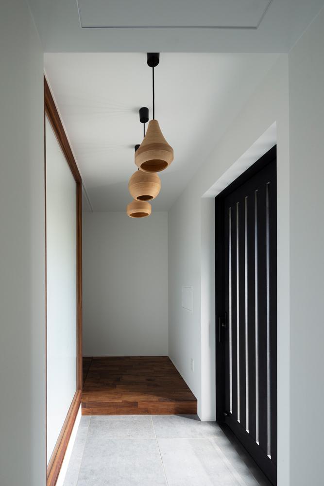 BUNACOのランプが並ぶ玄関。引戸はヘーベシーベの気密サッシ