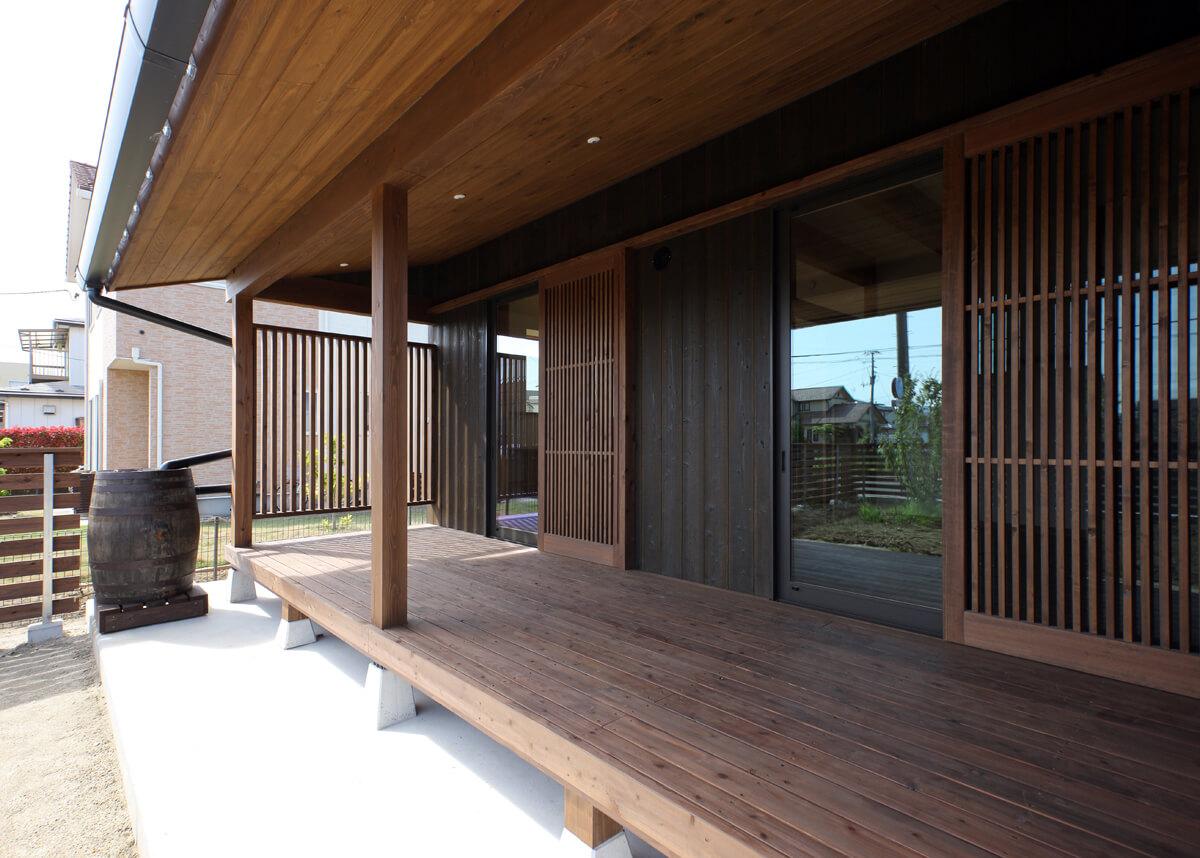 ご主人と奥さんの寝室前に設けた屋根付きのサンデッキ。網戸兼用の格子戸は、ご夫妻の要望により木製建具としている