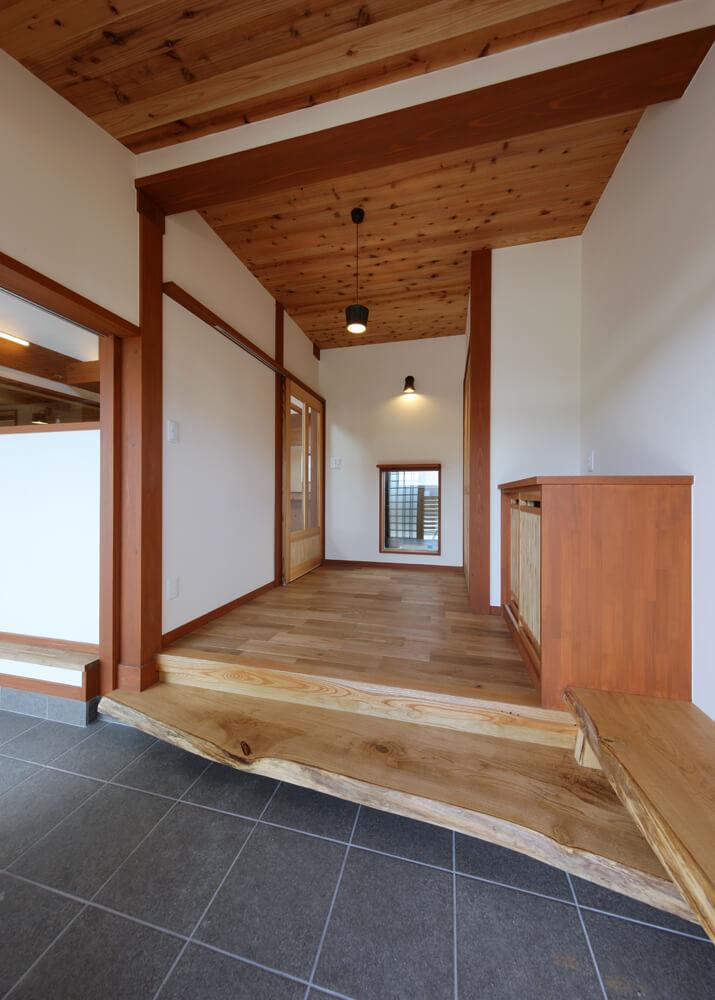玄関土間からホールを見る。正面のFIX窓からは坪庭 が見え、土間は左手のリビングへと続く