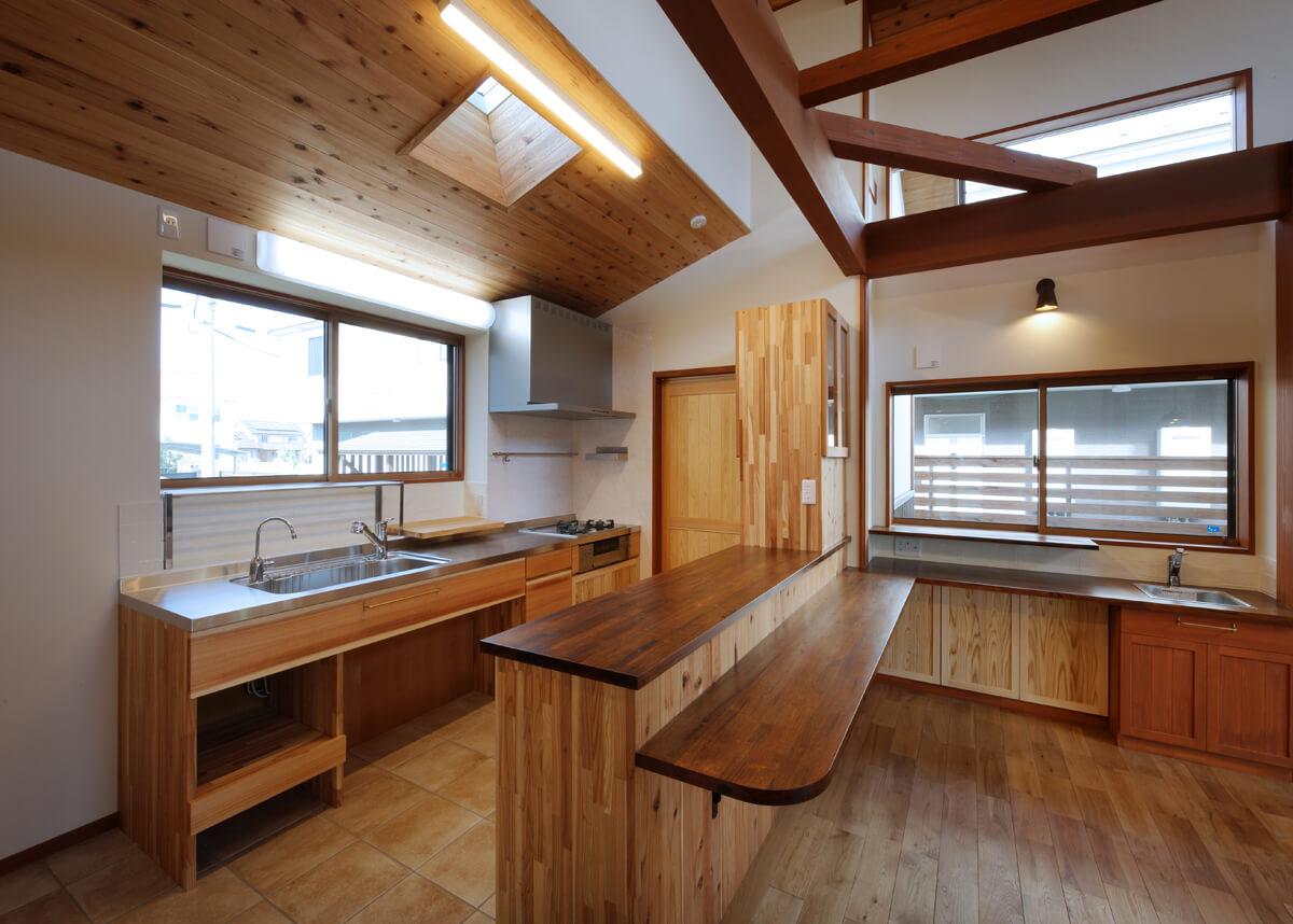 木工事による造作キッチンとカウンター収納。中庭を眺めながらちょっとした作業ができる主婦コーナーを窓際に設けた