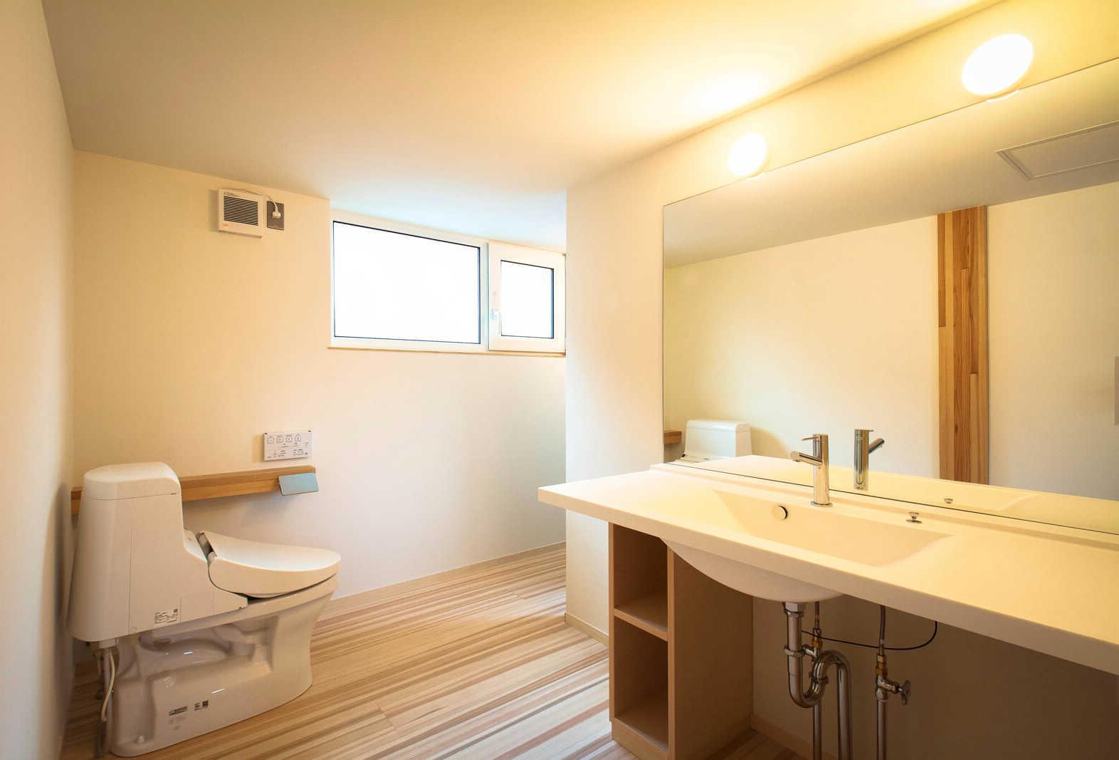 2階のトイレ兼ユーティリティ。奥に洗濯機と浴室入り口がある