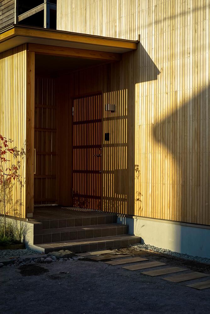 玄関ポーチ部分はファサードのラタンのピッチを変えることで、ほどよく光が入るようにした