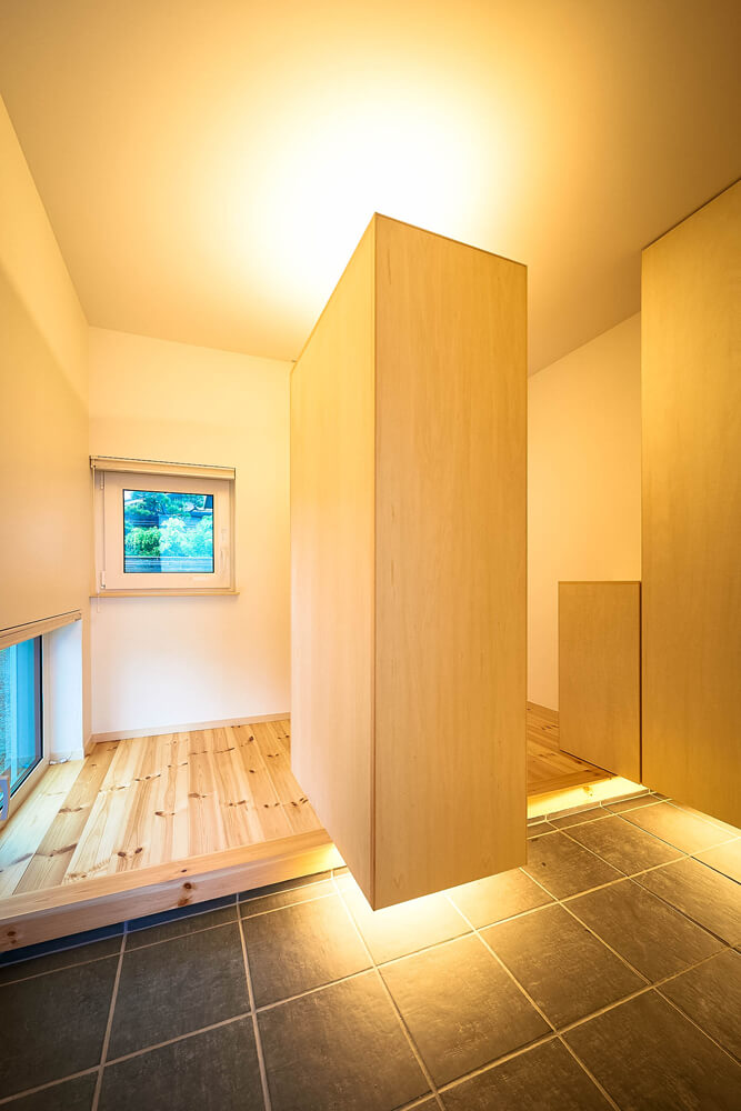 玄関には、庭が一望できる窓と、柔らかな明かりをとり入れるための地窓を設けた。お客様用とご家族用の2way動線