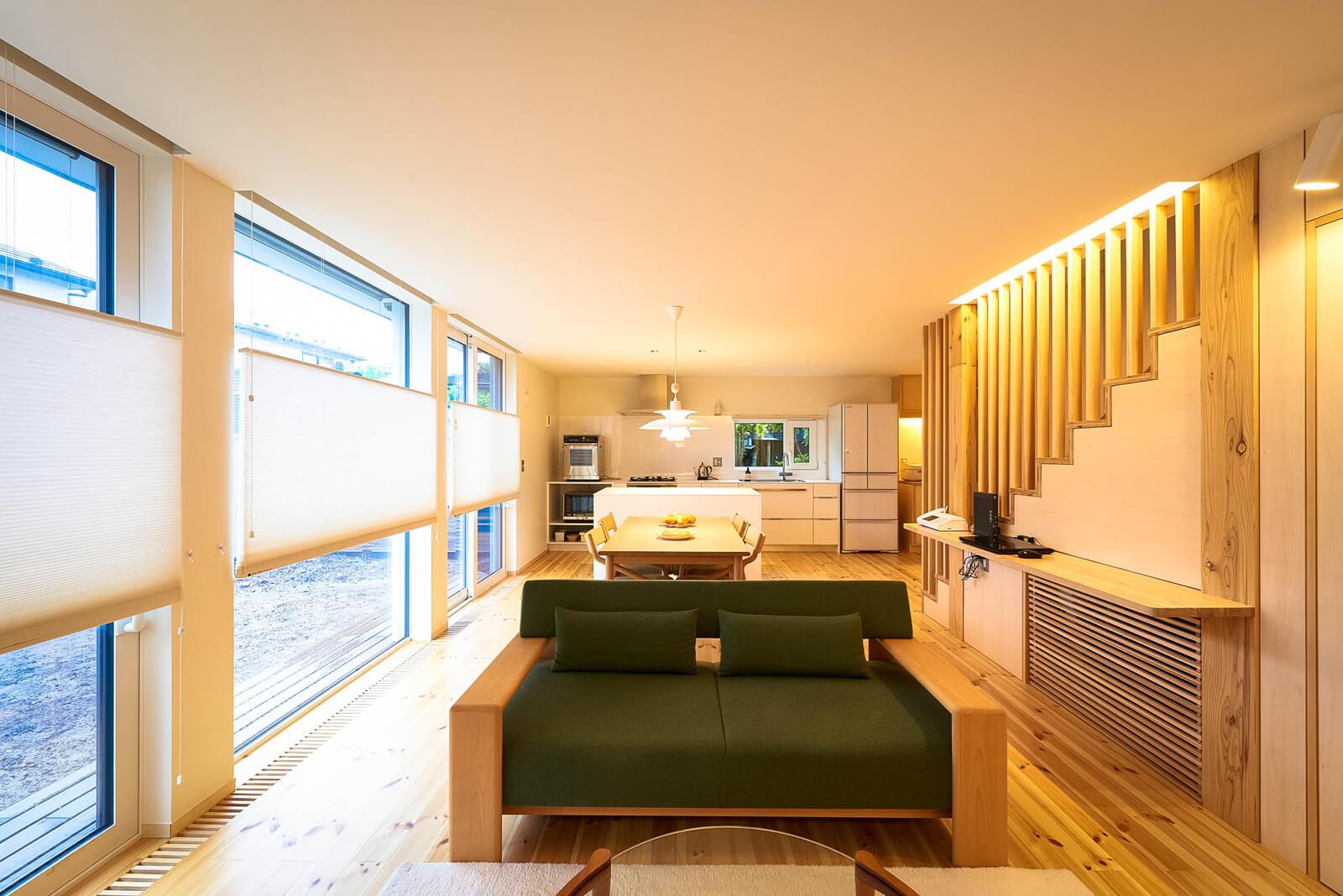 広々としたリビングは、階段下収納の一部にエアコンを設置。床下へ温風を送り込み、床暖房より快適な環境を生み出す。調光コントローラーと間接照明を主に使用して、目と心に優しい空間に