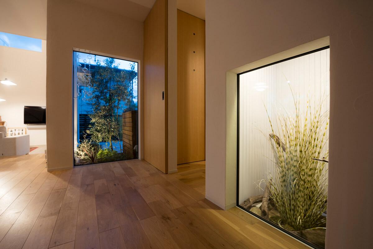 玄関に入ると正面に庭の植栽。ライトアップし、昼夜を問わずに庭を楽しめる