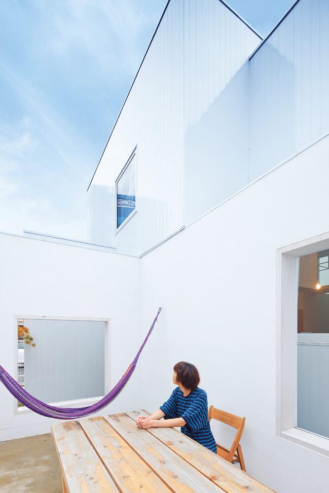 四方を背の高い壁に囲まれ、上部だけを開放したテラス。 包まれるような落ち着く感覚は、屋内と屋外、両方の特徴を併せ持つ不思議な空間だ
