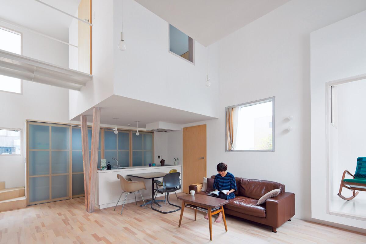 オープンなLDK。白を基調とした室内にランダムに配された窓から入る光が反射する。右手にはコンパクトなサンルーム、キッチン上に浮かぶのは来客用のゲストルーム