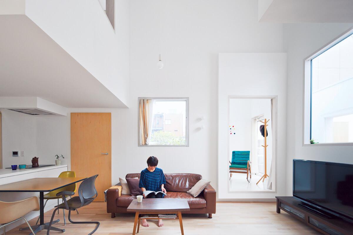 オープンなLDK。白を基調とした室内にランダムに配された窓から入る光が反射する