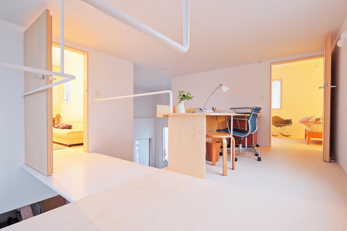 階段から2階全体を見る。吹き抜けに面して書斎のようなコーナーをはさみ、右奥は寝室、左手はゲストルームになっている
