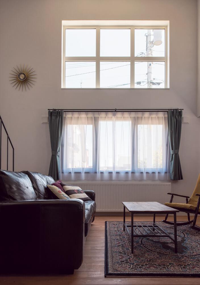 吹き抜けの窓からの陽光が漆喰壁に反射する明るいリビング