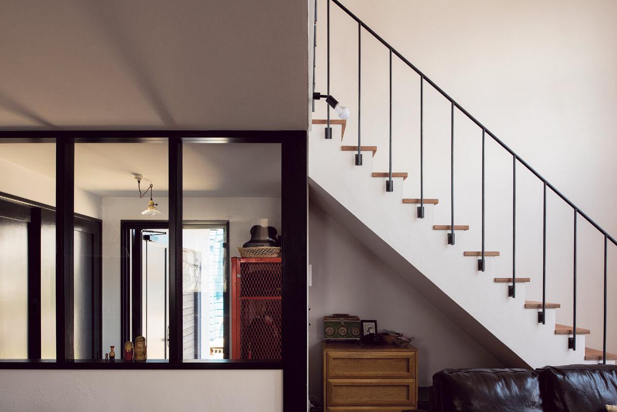 大好きなアンティークやユーズドの家具が似合う住まいにしたいと、壁や手すりの素材感や色合いにもこだわった。漆喰の壁とアイアンの階段手すり、ガラスの間仕切りのコントラストにセンスが光る