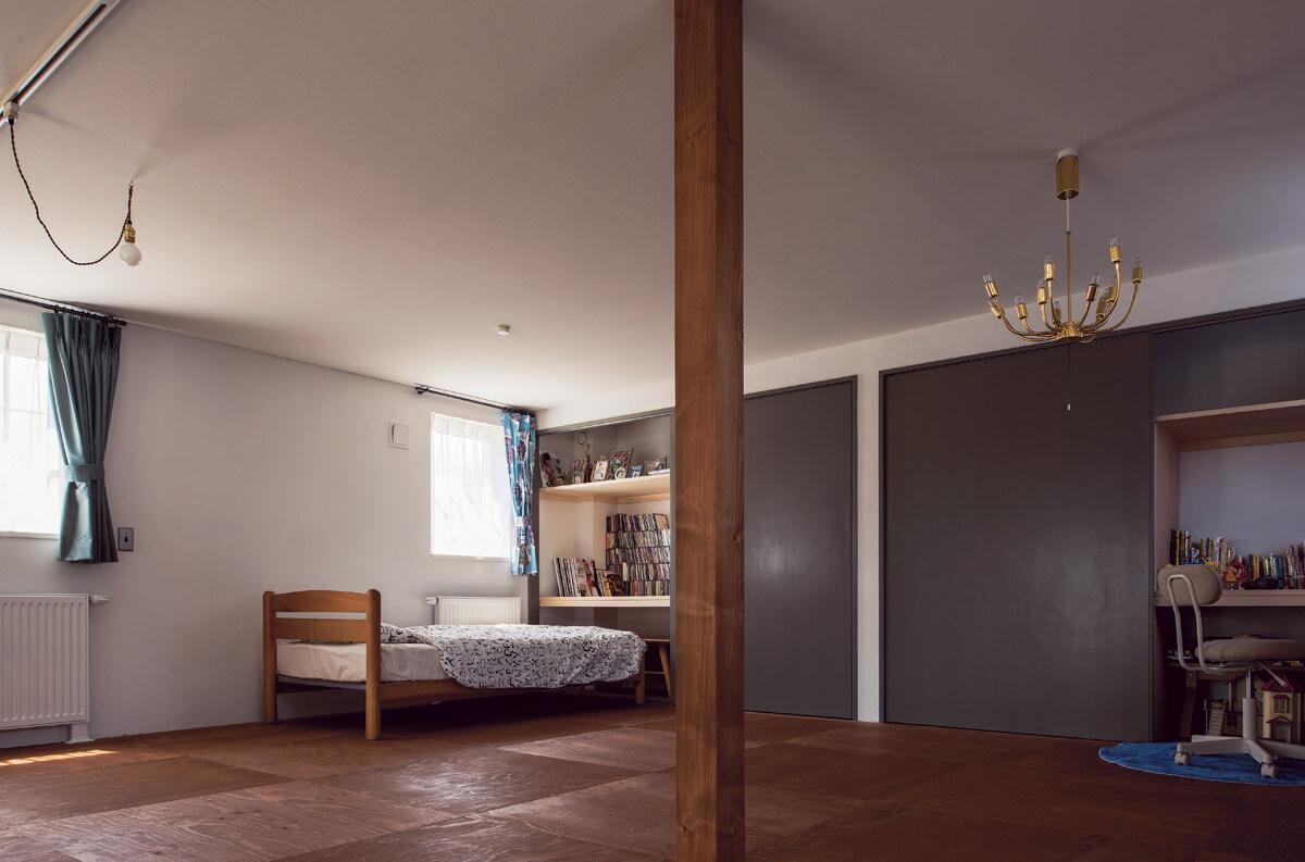 将来は間仕切ることもできる子ども部屋は、大きな戸を1枚にした収納とカラマツの構造材を市松に張った床がポイント