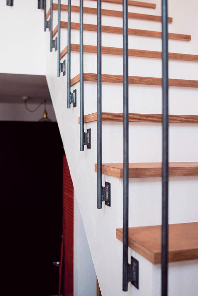 漆喰の壁とアイアンの 手すりが調和した 吹き抜け空間