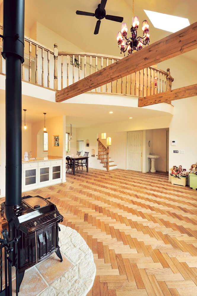 リビングには大きな吹き抜けが設けられ、開放感たっぷり。吹き抜けに大きくアールを描いて張り出した2階ホールの造作木製手すりのシルエットも美しい