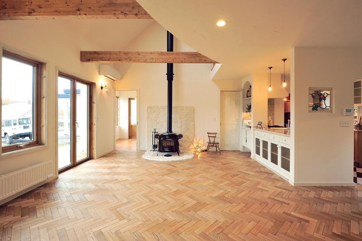 古材風に仕上げた梁、ヘリンボーン張りのレッドオークの無垢床、ダッチウエストの薪ストーブがかわいい空間をつくりだす