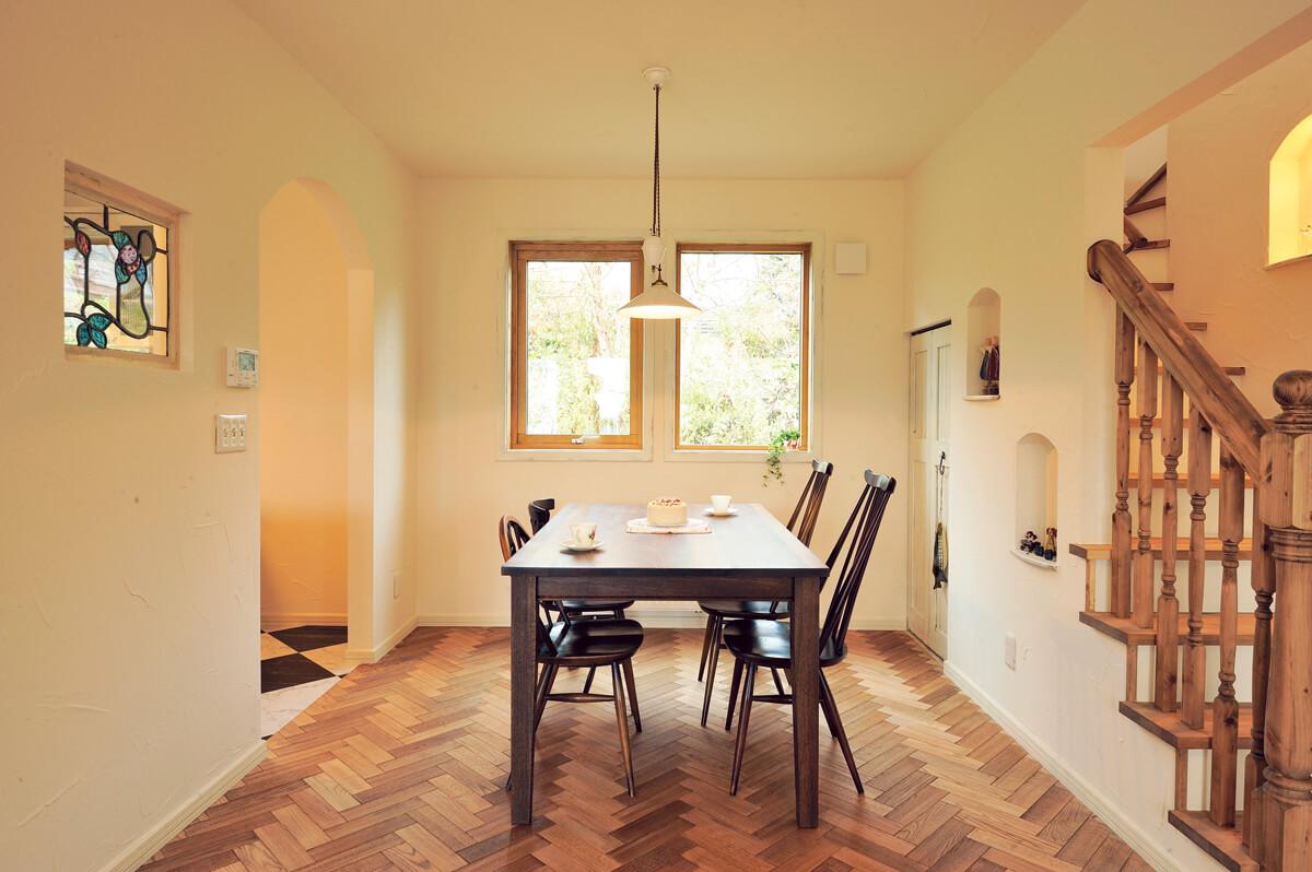 キッチン横に独立して設けたダイニング。窓からは裏側に広がる緑の借景が楽しめる。右奥の扉は、階段下収納