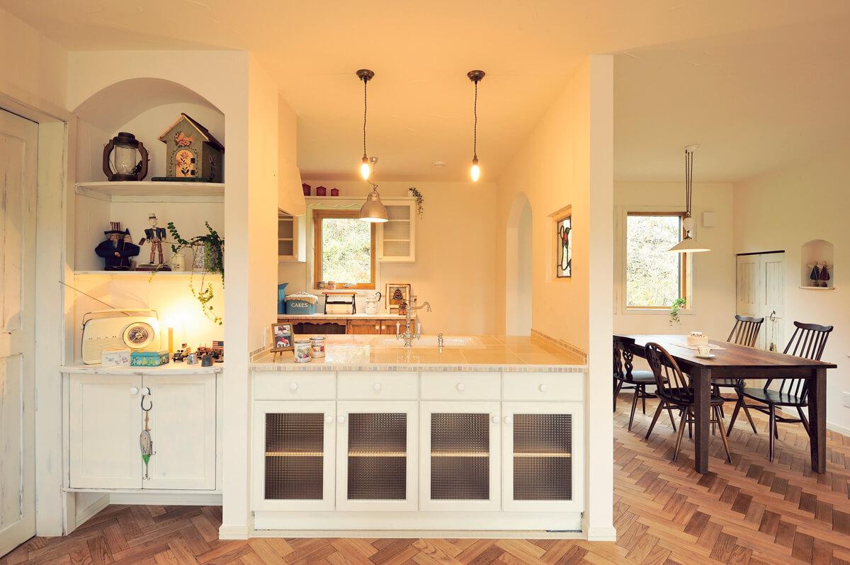 造作収納を備えた対面式キッチン。アンティーク・テイストのペンダントも奥さんのお気に入り