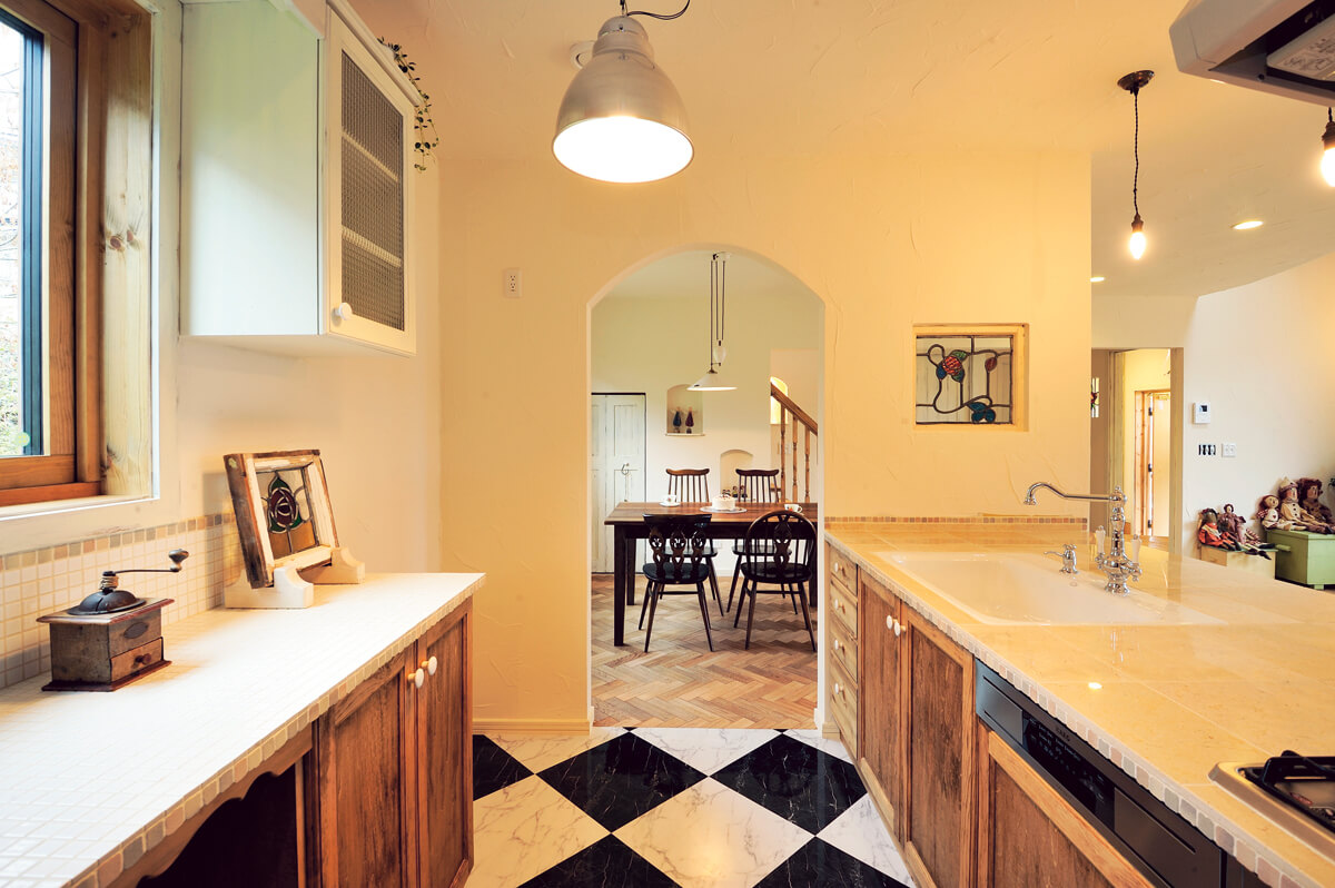 市松模様のフロアタイルを張った造作キッチン。奥には大容量のパントリーを備え、使い勝手も抜群