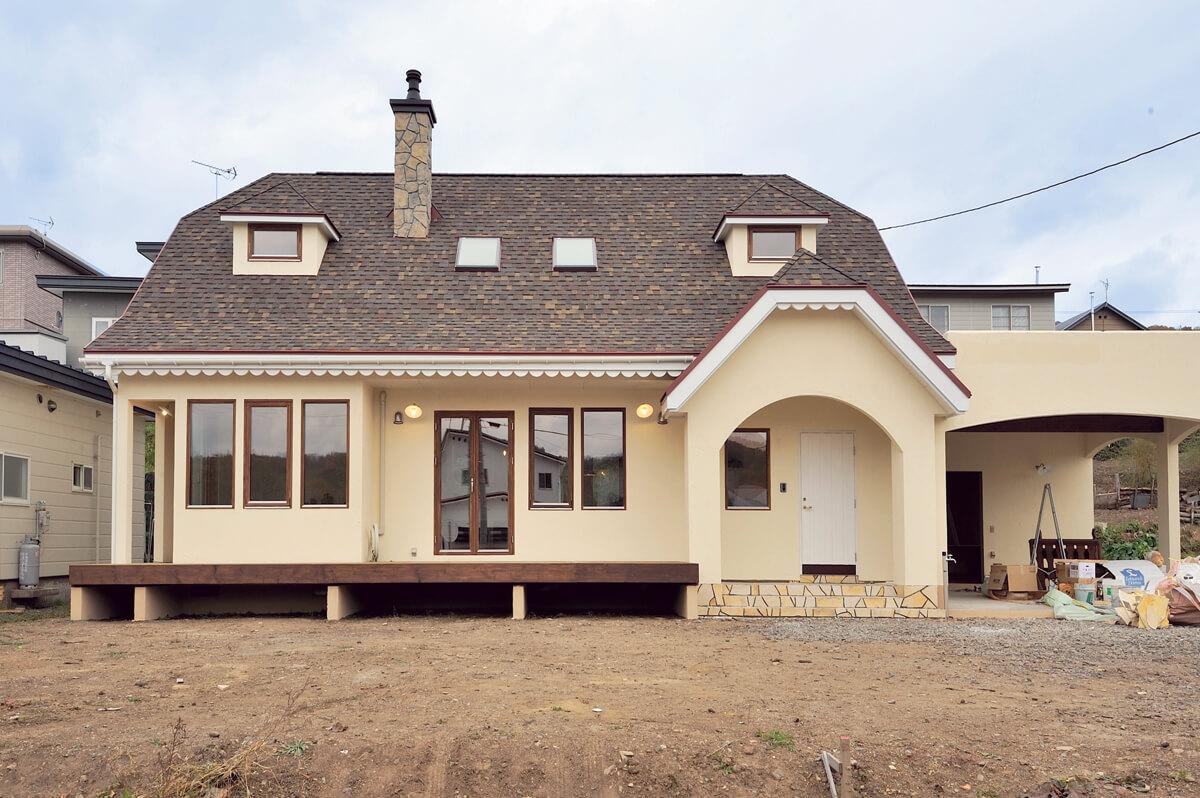 石張りの煙突にドーマーを備えた腰折れ屋根が目を引くYさん宅の外観。天窓を除き、開口部は断熱性能にすぐれた木製トリプルサッシを採用