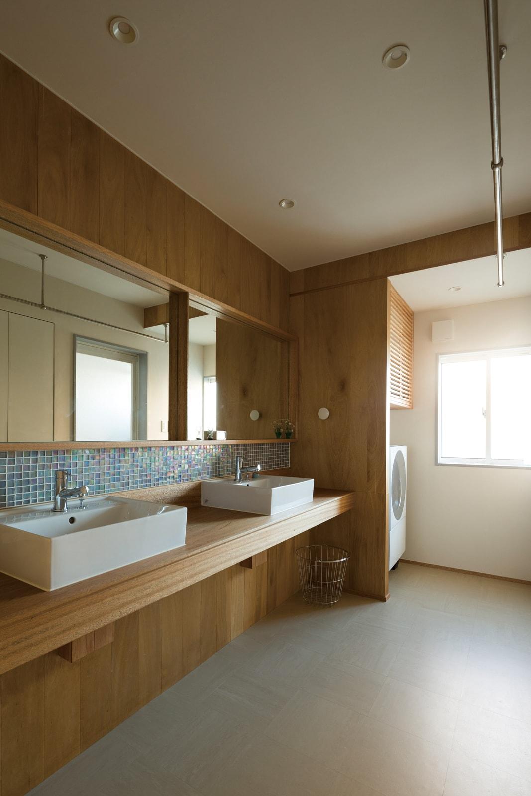 洗面スペースは奥さんたっての希望で横一面の大型鏡面に2つの洗面ボウルを設けた。木とタイルにセンスを感じる爽やかな空間