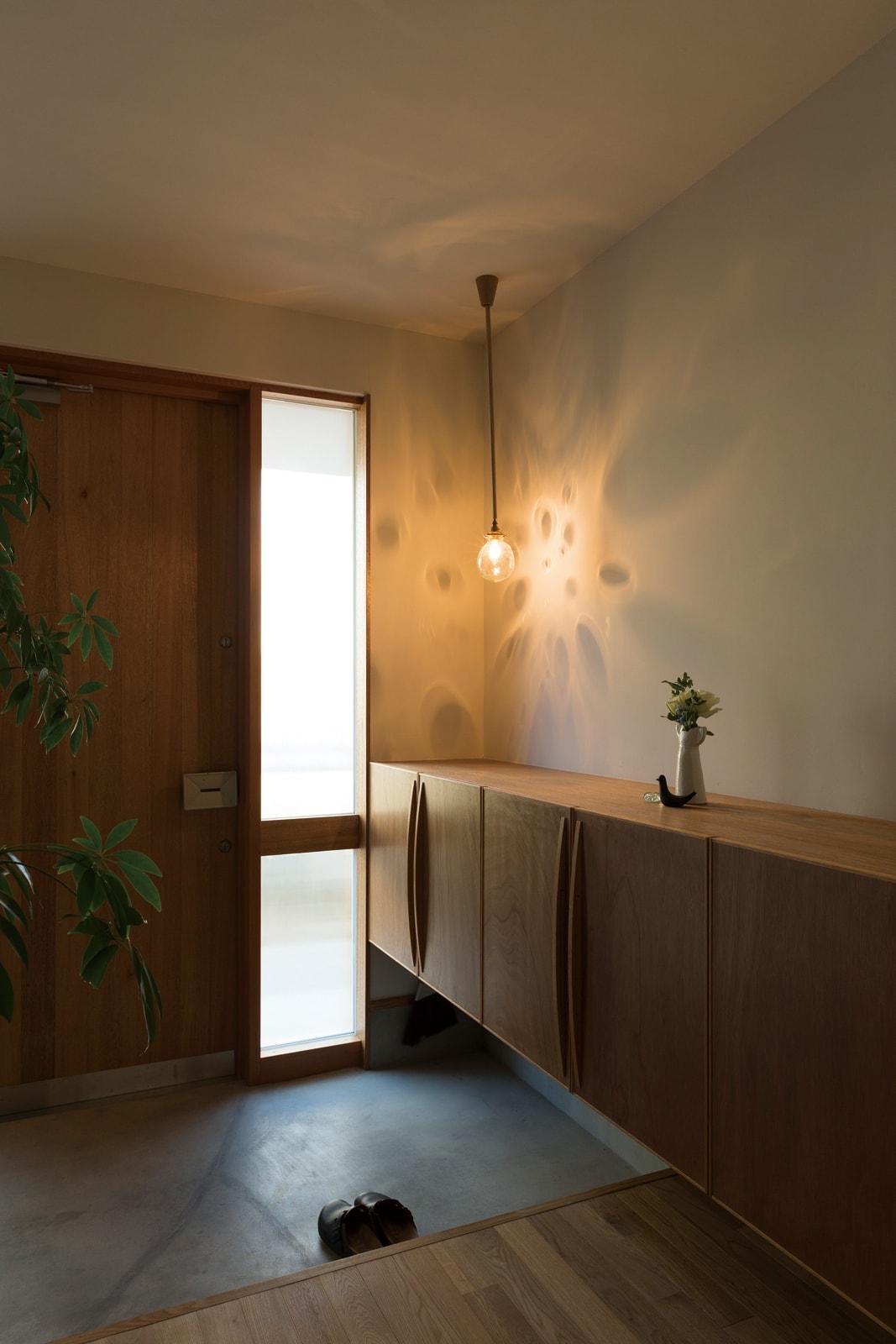玄関まわりは北欧テイストに。造作の収納は下部を空けて、高さのある傘やベビーカーも収納できるよう配慮されている
