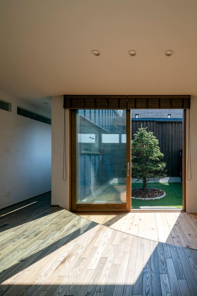 中庭前の床は、床材を変えて縁側的に。一段下げることでできた段差はちょっと腰かけるのにもちょうどいい高さ