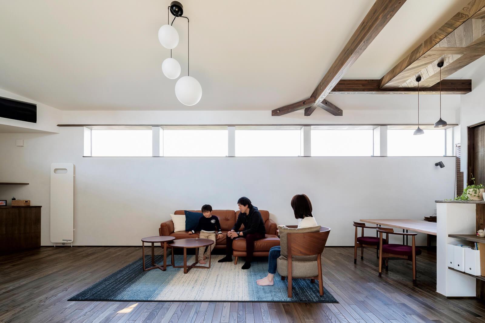 高い位置にある窓がプライバシーと採光の両方を確保。個性的な照明、一部梁現しの天井などが空間を引き締める