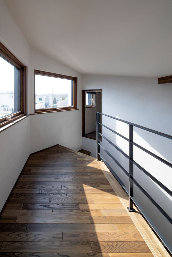 2階の大窓はプライバシーを守りつつの採光に欠かせない存在。2階廊下の床材の向きは1階と揃えた