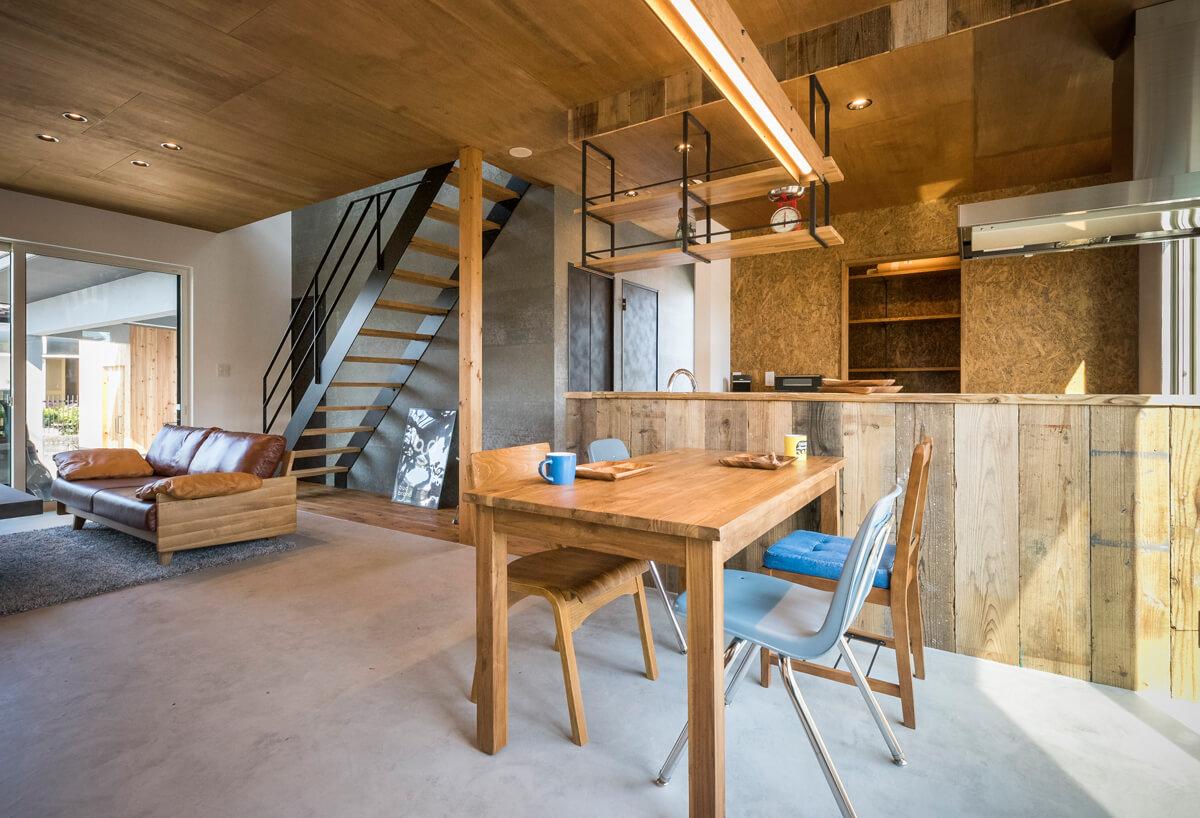 統一感のあるインテリアのLDK。キッチンの下がり壁と腰壁には、足場板を使用し、ラフ感を演出