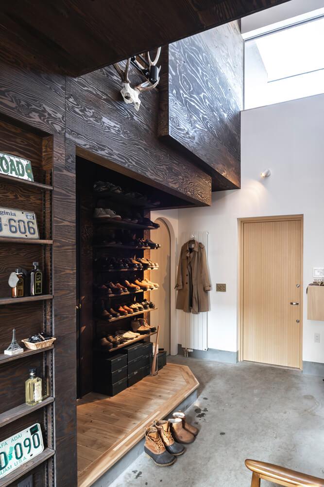 ハイサイドライトがあって伸びやかな吹き抜けの玄関ホール。靴が並んでいる棚の左右に屋内への出入り口がある